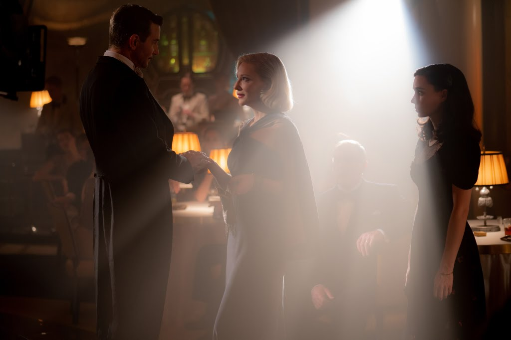 [Nightmare Alley Movie Still] In the spotlight: Cooper as Stanton, Cate Blanchett as Dr. Ritter, and Mara as Molly.